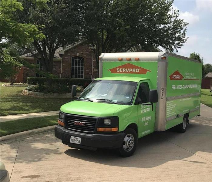 A SERVPRO truck sitting in front of a home.