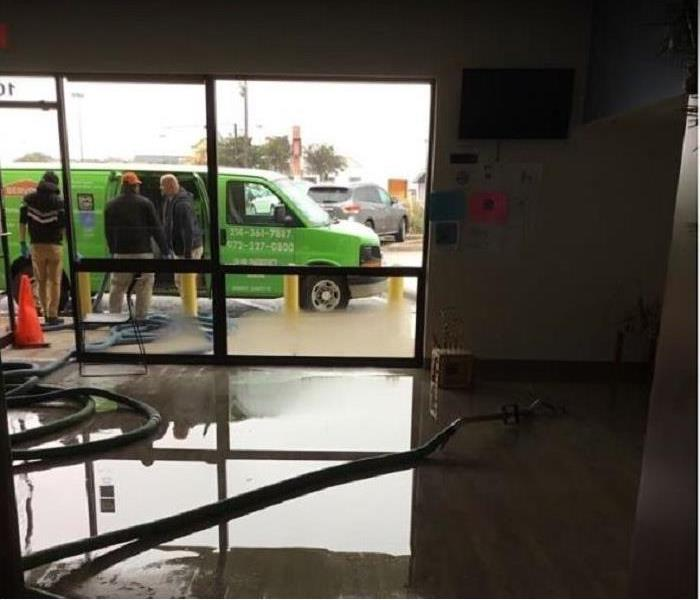 standing water in room. SERVPRO water extractors removing water; SERVPRO van and technicians outside
