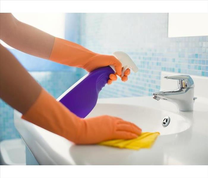Orange gloved hands holding a purple spray bottle and yellow rag wiping a sink