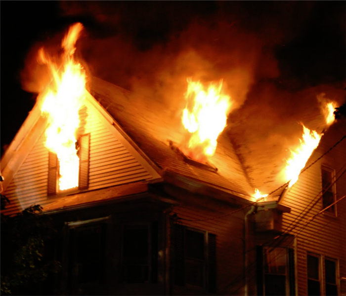 fire at night with flames coming out of the windows of a house