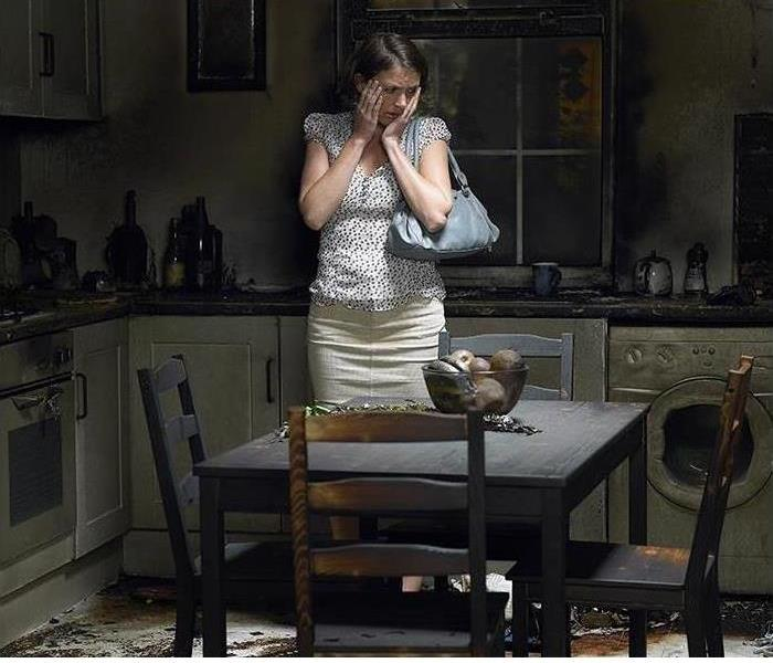 Woman looking dismayed while standing in fire damaged kitchen